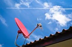 Röd satellit och blå sky arkivbilder