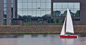 Röd segelbåt framme av en strandbyggnad Fotografering för Bildbyråer