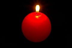 Röd sfärisk stearinljus i mörkret. Fotografering för Bildbyråer