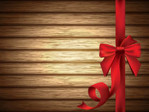 Röd silkeslen pilbåge med bandet över träbakgrund Royaltyfria Foton