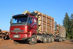 Röd Sisu 18E630 timmerlastbil som är klar att lasta av journaler Arkivbild