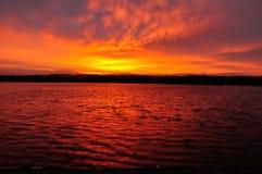 Röd sjö på soluppgång Arkivfoto