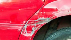 Röd skadad bil i forcerad olycka med skrapad målarfärg och den bucklade metallkroppen royaltyfri bild