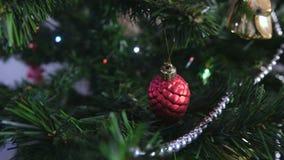 Röd skinande kotte på filialjulgranen Julgirland med ljus på julgranen arkivfilmer