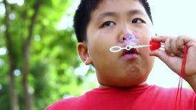 Röd skjortapojke som spelar blåsa bubblor stock video
