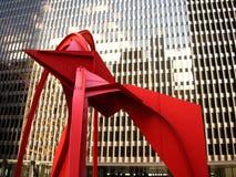 Röd skulptur framme av modern byggnad Arkivfoto
