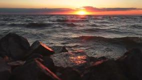 Röd sky över en stenig seashore vibrerande röd solnedgång för färgliggande arkivfilmer