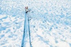 Röd släde på slutet av spåret i snö arkivbild