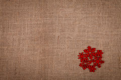 Röd snöflinga på säckväv Arkivbilder
