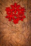 Röd snöflinga som prydnaden på trätabellen Arkivbild