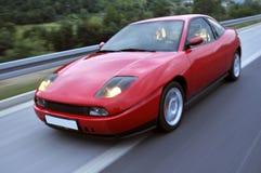 Röd snabb tävlings- bil på huvudvägen Arkivbild