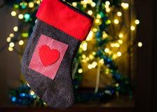 Röd socka med hjärta mellan julljus och den färgglade dekoren royaltyfria bilder