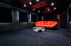 Röd soffa i mörkt rum arkivbilder