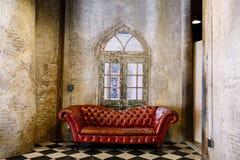 Röd soffa i theVintagerum royaltyfri foto