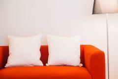 Röd soffa med kudde- och ljuslampan arkivbild