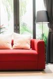Röd soffa med kudde- och ljuslampan fotografering för bildbyråer