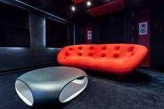 Röd soffa och modern tabell royaltyfri foto