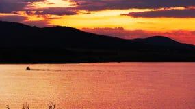 Röd sol för solnedgång bak bergöverkant arkivbild
