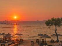 Röd sol för turkisk fjärdsolnedgångferie över vattnet arkivfoton
