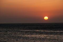 Röd sol och hav på solnedgången Arkivbild