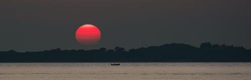 Röd sol på solnedgången på havet med fiskebåten Fotografering för Bildbyråer