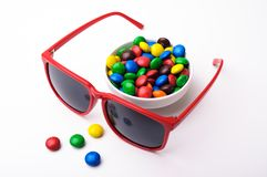Röd solglasögon och färgrika candys Arkivfoto