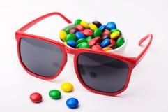 Röd solglasögon och färgrika candys Royaltyfri Foto