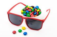 Röd solglasögon och färgrika candys Arkivbilder