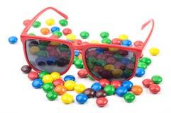 Röd solglasögon och färgrika candys Royaltyfria Bilder