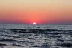 Röd solnedgång över Östersjön Arkivbild