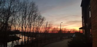 R?d solnedg?ng ?ver floden med f?rglutningmoln royaltyfri bild