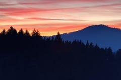 Röd solnedgång för brand över berg Arkivbilder