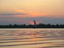 Röd solnedgång med segelbåten och glödvatten arkivfoton