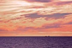 Röd solnedgång och kontur av ett fartyg Arkivfoton