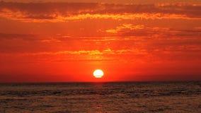 Röd solnedgång och moln på havet royaltyfria bilder