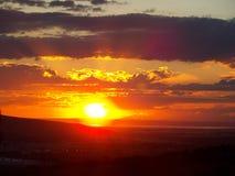 Röd solnedgång som skapar flamma moln Arkivbild