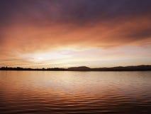 Röd soluppgång över den Tauranga hamnen, Arkivfoto