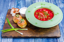 Röd soppa i en grön platta, rullar, bacon, lökar och sås arkivfoton