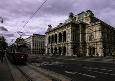 Röd spårvagn som är främst av den Wien operan royaltyfria bilder