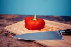 Röd spansk peppar och kniv på skärbräda Arkivbild