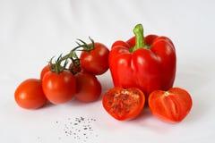 Röd spansk peppar, röda körsbärsröda tomater, salt svart, vit bakgrund Arkivfoto
