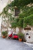Röd sparkcykel för italiensk tappning framme av ett gammalt hus Fotografering för Bildbyråer