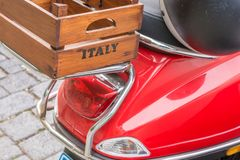 Röd sparkcykel med en träask på bagagehyllan med inskriften Italien arkivfoton