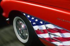 Röd sportbil med amerikanska flagganklippning Arkivbild