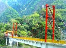 Röd stålbro i bergen i Taiwan Korsa klyftan royaltyfri fotografi