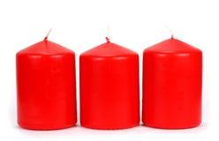 Röd stearin tre på en vit bakgrund Fotografering för Bildbyråer