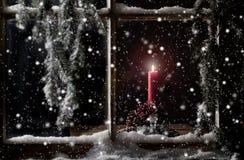 Röd stearinljus i fönster Arkivbild