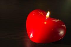 Röd stearinljus i form av hjärta Arkivfoton