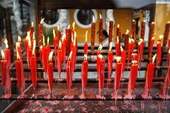 Röd stearinljus på buddhismtemplet Royaltyfri Foto