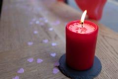 Röd stearinljus som isoleras med rosa hjärtakonfettier royaltyfri foto